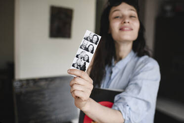 Woman holding photos of herself with her boyfriend - EYAF00268