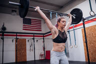 Young woman lifting barbell in gym - ISF22059
