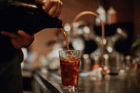 Barista pouring fruit juice into drinking glass on cafe counter, cropped low key - ISF22092