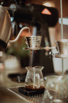 Boiled kettle water pouring into coffee filter and dripping into jug on cafe counter, shallow focus - ISF22095