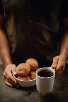 Barista placing black coffee and doughnuts on cafe counter, cropped shallow focus - ISF22098