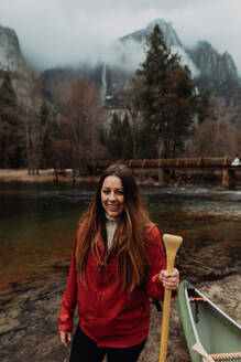 Young female canoeist on riverbank, portrait, Yosemite Village, California, USA - ISF22104