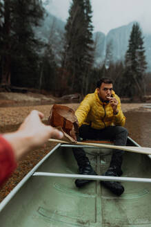 Young canoeing couple sharing snacks on canoe, personal perspective, Yosemite Village, California, USA - ISF22107