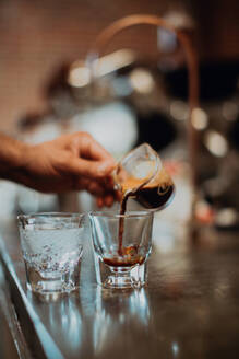 Barista pouring fresh coffee into drinking glass on cafe counter, detail of hand - ISF22125