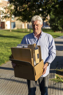 Senior man recycling cardboard carrying cardboard box - AFVF03448
