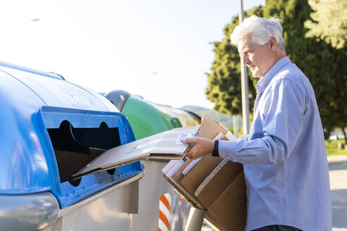 Senior man recycling cardboard in paper bank - AFVF03451