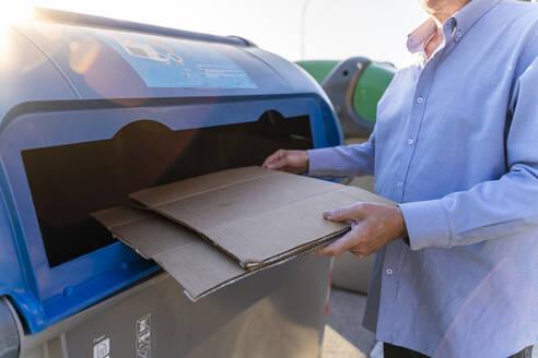 Senior man recycling cardboard in paper bank - AFVF03454