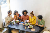 Group of friends having lunch in a restaurant - AFVF03489