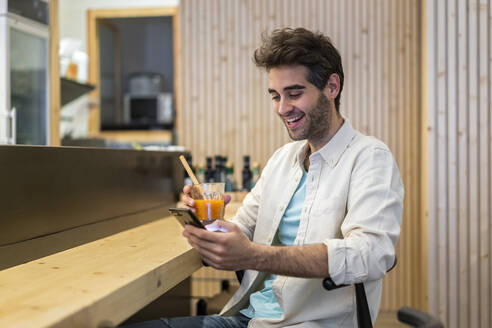 Man with cell phone sitting at the counter of a bar having a drink - AFVF03498