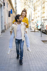 Man giving girlfriend a piggyback ride on pavement in the city - AFVF03504