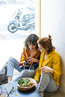 Two young women in a cafe looking at cell phone - AFVF03516