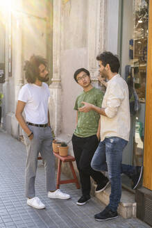 Three young men talking in the city - AFVF03531