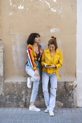Two young women with cell phone standing at a building - AFVF03534