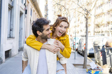 Man giving girlfriend a piggyback ride on pavement in the city - AFVF03537