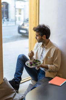 Man eating a salad sitting at the window in a restaurant looking out - AFVF03552