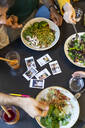 Group of friends having lunch in a restaurant with instant photos on table - AFVF03555