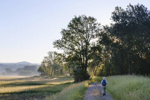 Frau mit Rucksack auf Weg am Waldrand bei Sonnenaufgang, Naturschutzgebiet Isarmündung, bei Deggendorf, Niederbayern, Bayern, Deutschland - SIEF08718