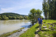 Rear view of man and woman walking by River Isar during sunny day, Bavaria, Germany - SIEF08733
