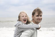 Porrait of smiling father carrying his carefree daughter piggyback at the sea - EYAF00273