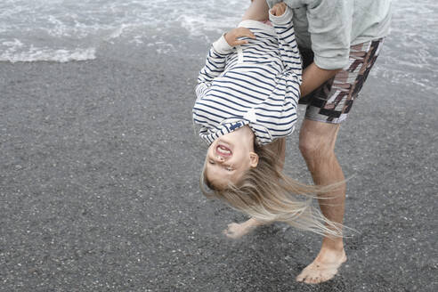 Father playing with his daughter on the beach - EYAF00276