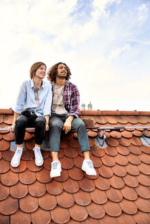 Young couple sitting on rooftop and looking at distance - SUF00568