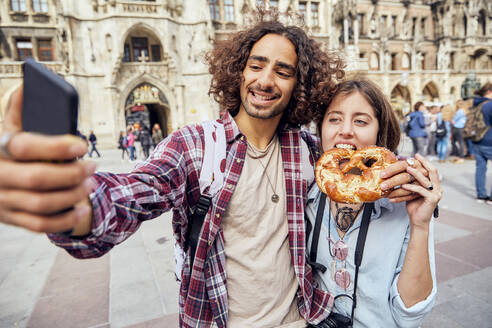 Young couple taking a selfie with brezel in the mouth, Munich, Germany - SUF00583