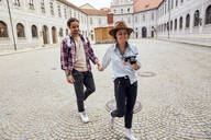 Young tourist couple walking in courtyard of Munich Residenz, Munich, Germany - SUF00586