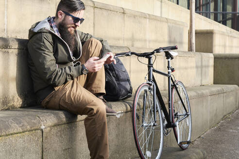 Side view of bearded mid adult man using smart phone while sitting on steps in city - IGGF01187