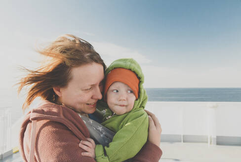 Mother wearing her baby boy in a baby carrier on board of a sea ferry, Kiel, DE - IHF00158