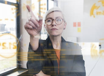 Businesswoman touching glass wall with data in office - UUF17907