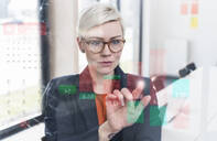 Businesswoman touching glass wall with data in office - UUF17910