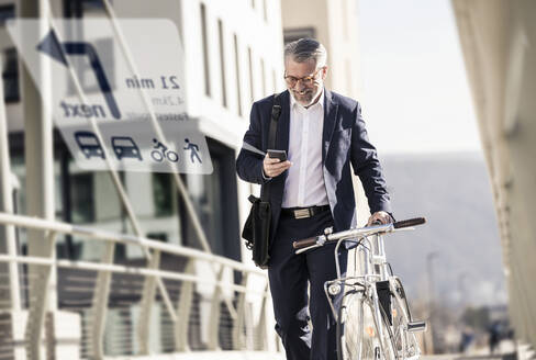 Smiling mature businessman with bicycle using cell phone for navigation in the city - UUF17913