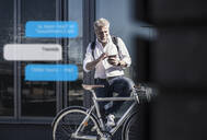Smiling mature businessman with bicycle using cell phone for messaging in the city - UUF17916
