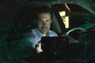 Businessman using navigation device in car at night - UUF17922