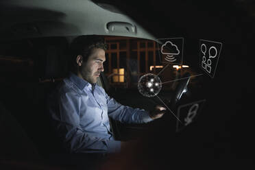 Businessman using device in car at night surrounded by internet symbols - UUF17925