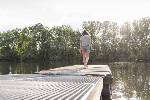 Young woman walking on jetty at a remote lake - UUF17928