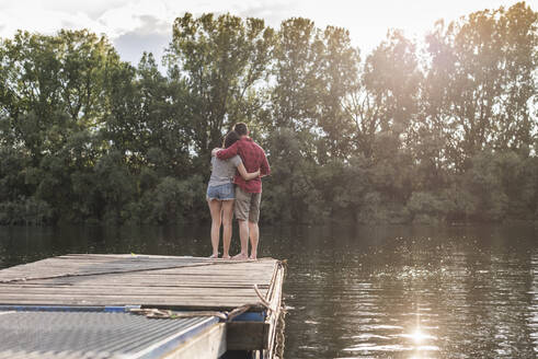 Young couple embracing on jetty at a remote lake - UUF17934