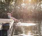 Happy young couple having a drink and splashing with water on jetty at a remote lake - UUF17937