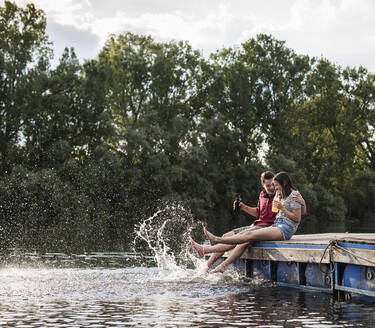 Young couple having a drink and splashing with water on jetty at a remote lake - UUF17940