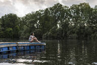 Relaxed woman sitting on jetty at a remote lake - UUF17943