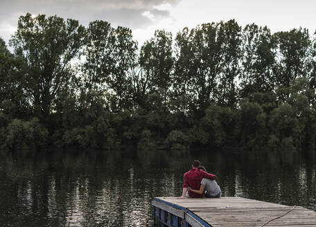 Young couple embracing on jetty at a remote lake - UUF17946