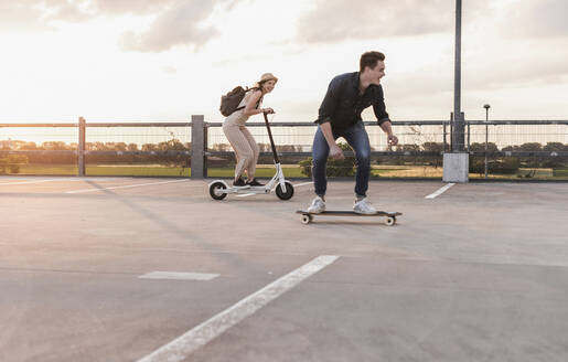 Young man and woman riding on longboard and electric scooter on parking deck at sunset - UUF17970