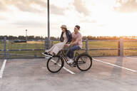 Happy young couple together on a bicycle on parking deck at sunset - UUF17979