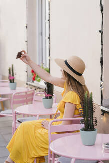 Lithuania, Vilnius, Young woman taking selfie in hipster outdoor cafe - AHSF00578