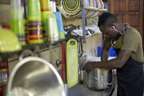 Young man washing dishes in restaurant kitchen, South Africa - VEGF00331