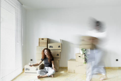 Young woman sitting in new home with glass of red wine while friend is moving fast with cardboard box - JPTF00226