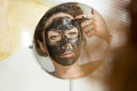 Mirror image of young woman applying facial mask at home - JPTF00235
