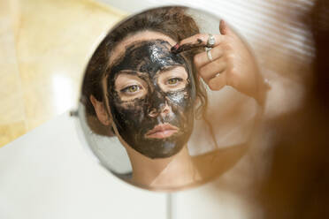 Mirror image of young woman applying facial mask at home - JPTF00235