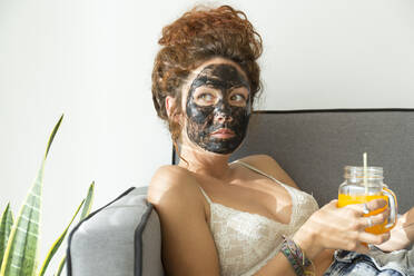 Young woman wearing facial mask and having a drink at home - JPTF00238