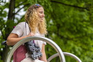 Smiling young woman with  inline skates at a skatepark - STSF02048